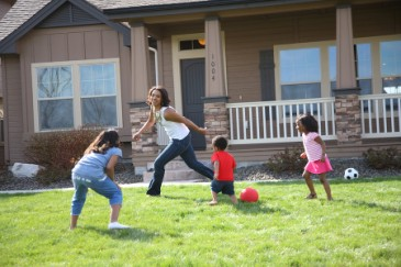 Fun Family Fitness, Mom and three kids playing ball or tag outdoors for exercise