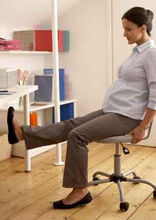 pregnant woman stretching legs at desk job