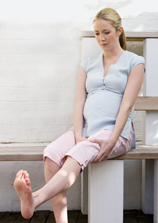 pregnant woman relieving leg cramps