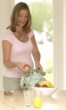 pregnant woman packing healthy lunch snacks