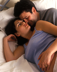 pregnant couple intimate in bed