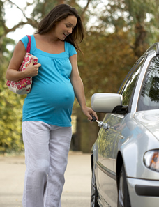 Pregnant woman getting in car