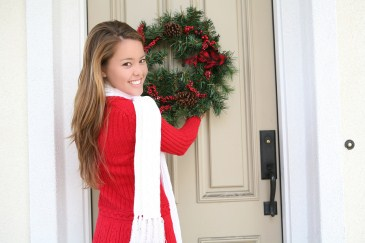 traditional christmas activity, girl hanging holiday wreath