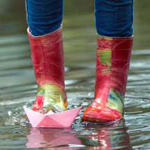 rainboots jumping in spring puddle
