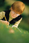 Boy writing outside