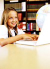 Girl in library with computer and globe