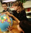 Three students looking at a globe