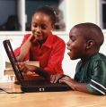 Elementary-aged boy and girl working on laptop in classroom