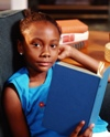 Young girl reading book in chair