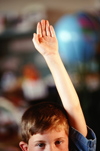 Young male student raising hand