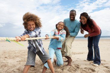 black family playing on beach