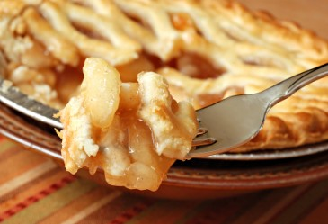 Mouthful of apple pie on fork, with pie in background.