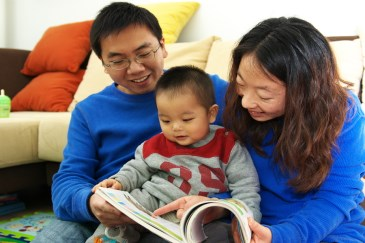 parents reading to baby boy