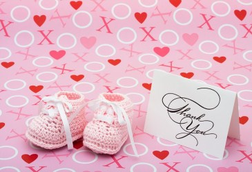 Pink booties and thank you card against pink backdrop