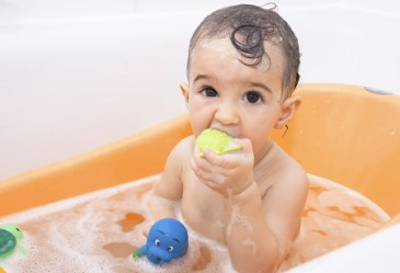 Young Child taking a bath and putting bath toy in mouth