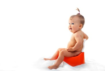 Baby on toilet against white backdrop