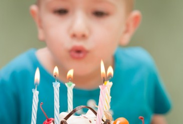 Close up of cake with boy blowing out candles