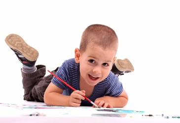 Young boy finger painting against white backdrop