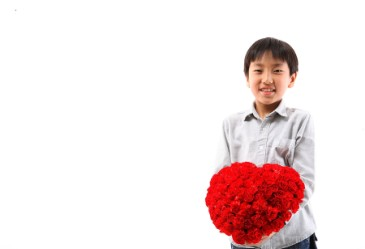 Young Asian boy with rose bouquet against white back drop