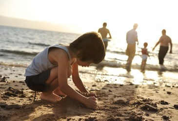Child playing in the sand with family in the background