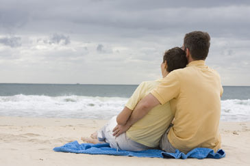 Couplesittingonbeach,hugging