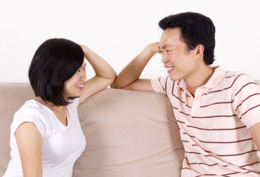 Asian couple sitting on couch talking