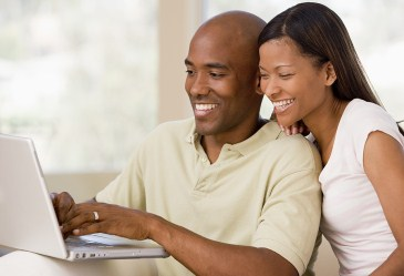 Young couple laughing over laptop