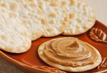 Cracker with peanut on plate with crackers in background.