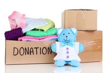 Box of donated clothes against white background