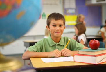 Young student sitting at desk smiling