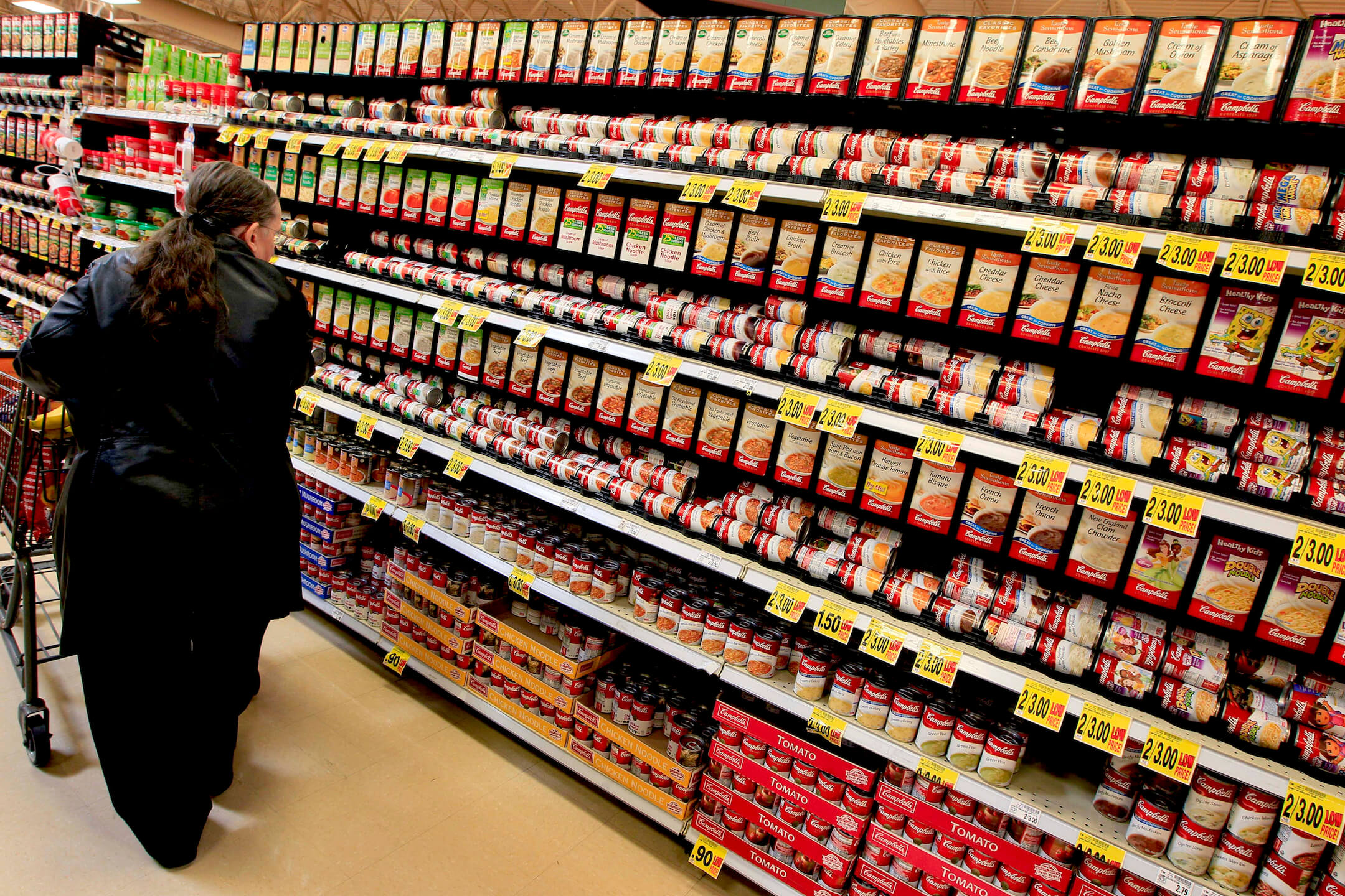 image of woman shopping in the soup aisle of groccery store