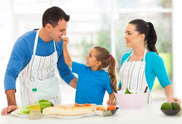 Mother, father, and daughter cooking meal in kitchen