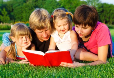 Smiling family laying on grass reading book