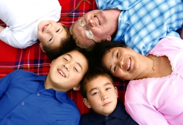 Family laying down on blanket smiling up at camera