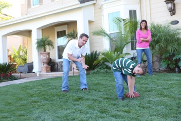 Keeping Your Husband Healthy, Man and son playing football in yard for exercise