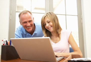 Father and teen daughter using computer