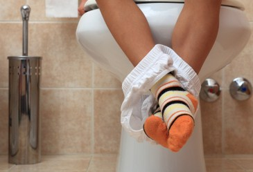 Child's feet dangling from toilet
