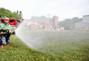 Little boy having fun spraying fire house