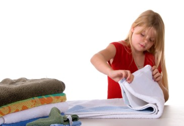 Young girl folding towels against white back drop.