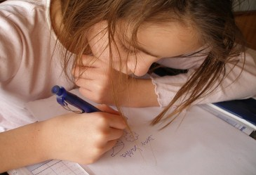 Closeup of young girl writing letter