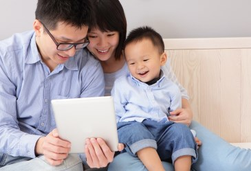 Happy family sitting on couch using tablet