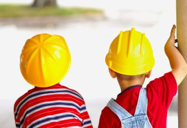 Two young boys in yellow construction hats