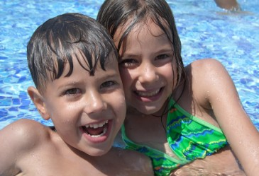 Two kids smiling in outdoor pool
