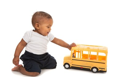 Baby playing with toy school bus