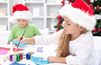 children making Christmas crafts in Santa hats