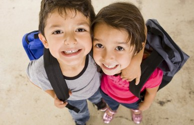 Two kids wearing backpacks smiling at camera