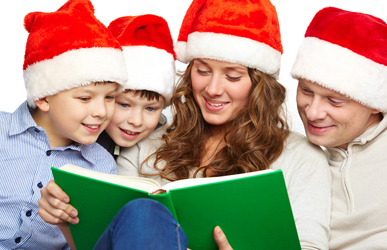 family reading Christmas book in Santa hats