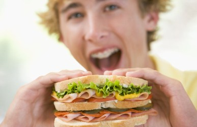 teen boy with big appetite eating sandwich