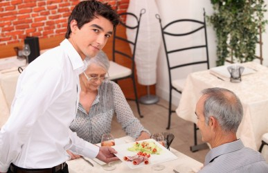 Young waiter serving older customers
