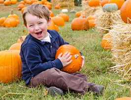 boy in Halloween pumpkin patch